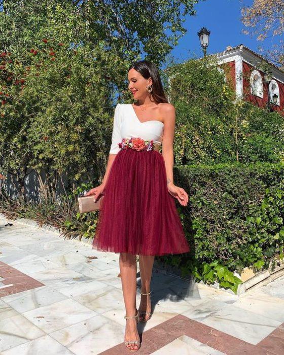 Chica en un jardín modelan su outfit con falda de tul en color vino