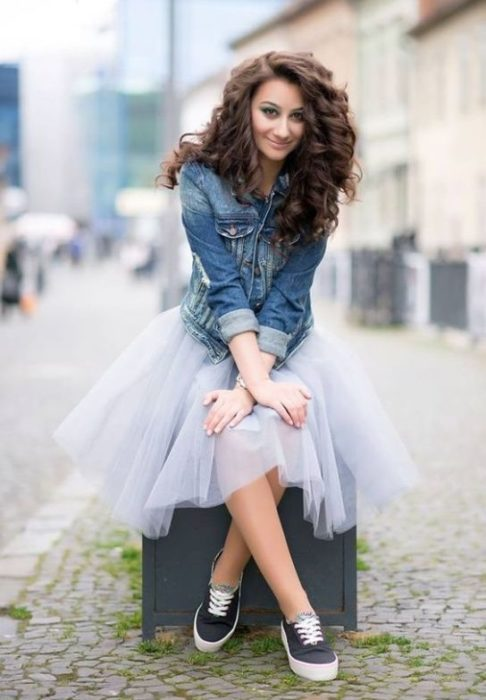 Chica con falda de tul en tono azul sentada en un banco a mitad de avenida