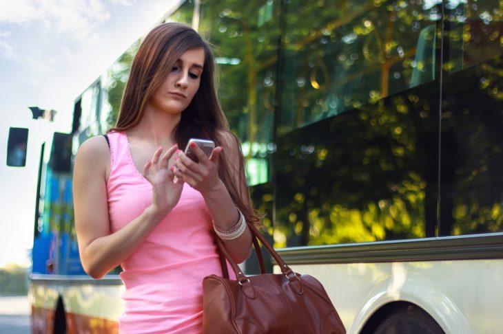 una mujer de blusa rosa con su bolsa colgada revisa su celular