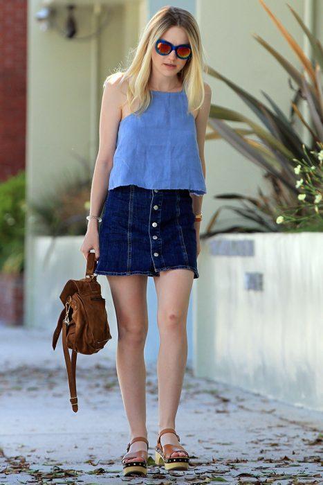 Chica caminando por la calle con top azul y falda corta de mezclilla