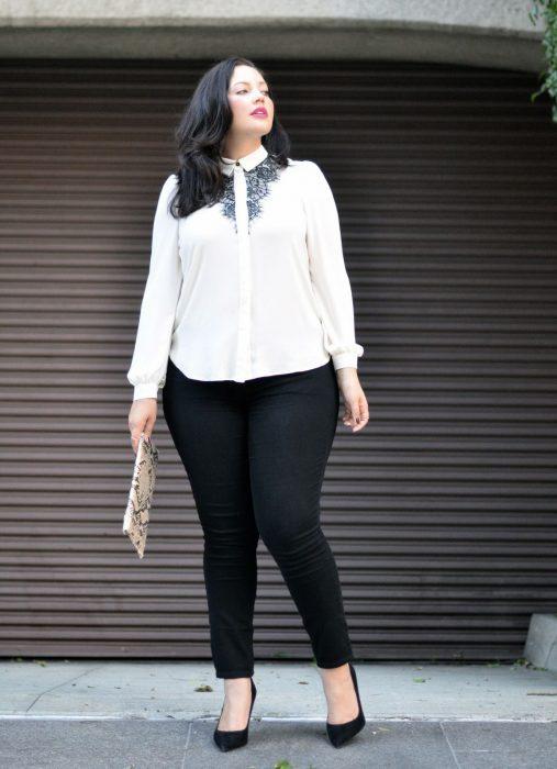 Chica modelando unos leggins negros y blusa de botones blanca