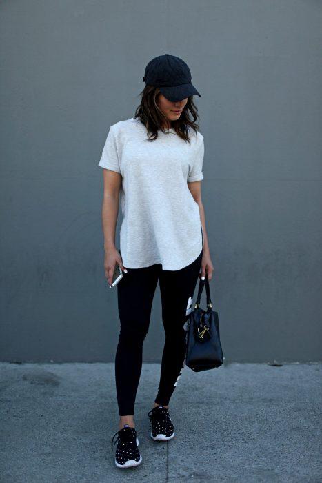 Chica en pared gris, con blusa blanca holgada, leggins negro, tenis deportivos, cachucha negra y en mano su celular y bolso negro