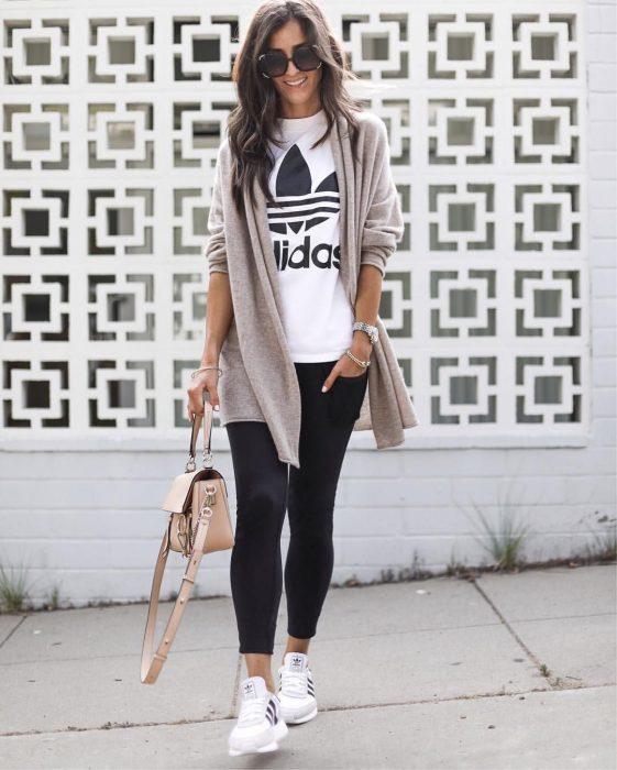 Chica posando enfrente de una pared con leggins negros, camisa blanca y estampado de addidas, con tenis blancos
