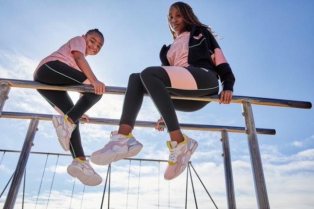 Una niña y una mujer modelando la ropa deportiva de la nueva colección de Puma x Barbie