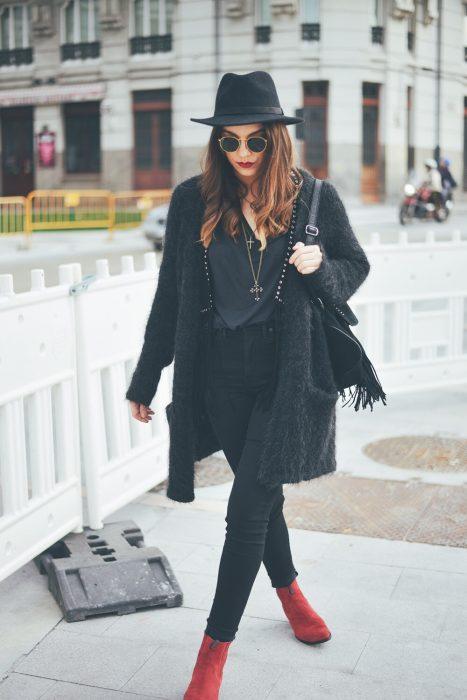 Chica caminando por la ciudad con outfit y sombrero negro y botines rojos