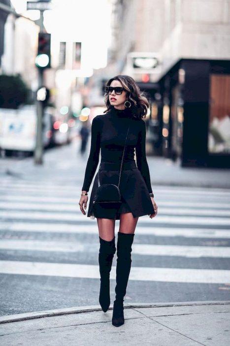 Chica paseando por la calle con falda corta y blusa de cuello alto negro y botas largas