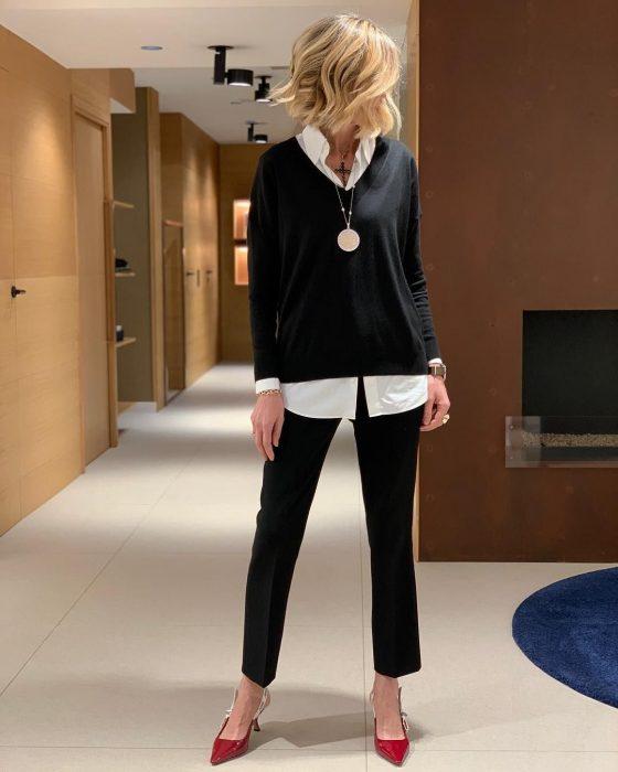 Chica posando con su atuendo en negro con blusa y zapatillas rojas