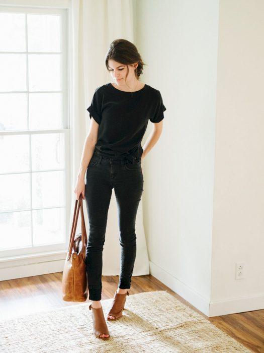 Mujer con atuendo negro, bolsa y calzado de color café