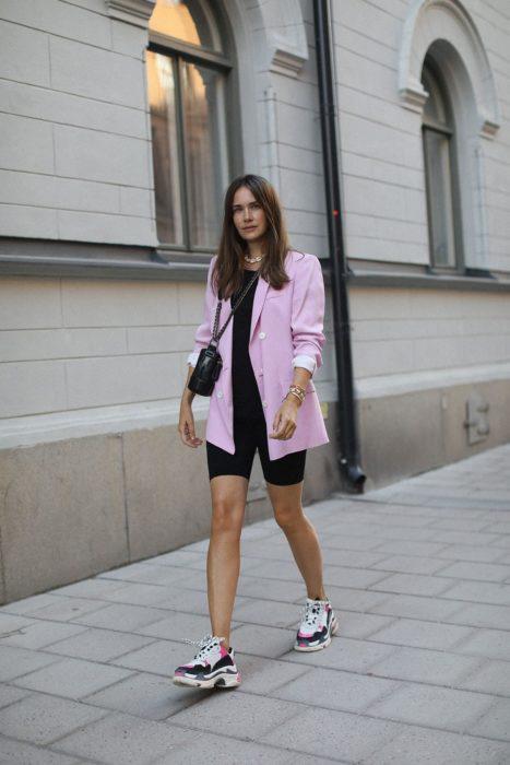 Chica usando unas mayas para ciclista con un blazer rosa y uglye shoes