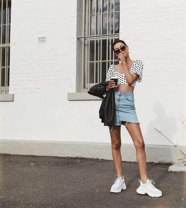 Chica usando una falda de jean, blusa blanca con estampados en negro y unos ugly sneakers de color blanco