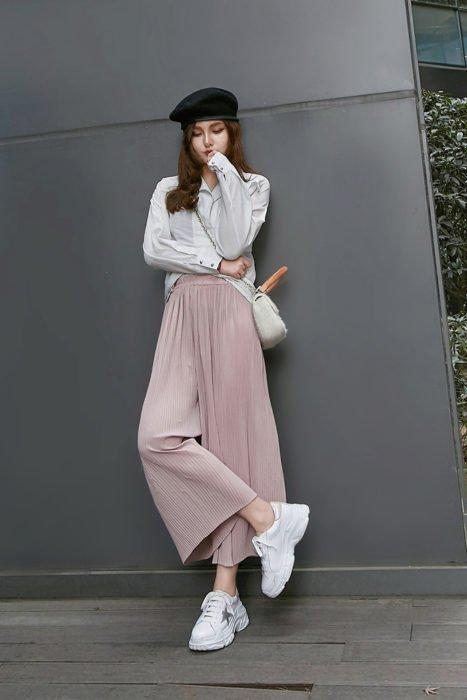 Chica usando un pantalón culotte de color rosa palo con blusa blanca, boina francesa y tenis ugly en color blanco