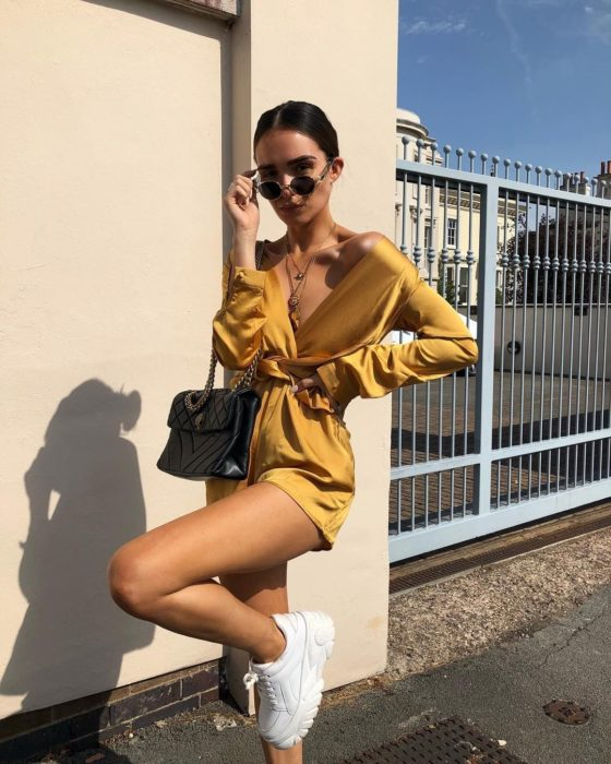 Chica usando un jumpsuit de seda color amarillo con unos tenis ugly de color blanco