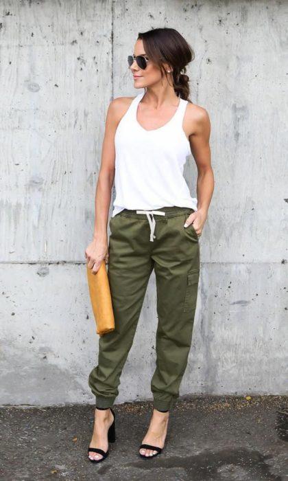 Chica usando un jogger pant de color verde militar con una blusa de tirantes de color blanco