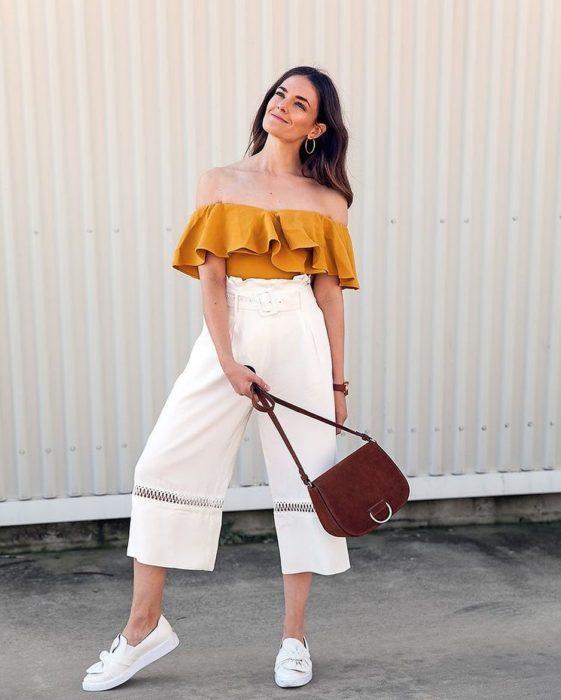 Chica usando un pantalón de color blanco y holgado con tenis y un top de color mostaza