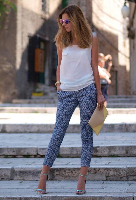 Chica usando un pantalón pescador de color azul con círculos y top blanco