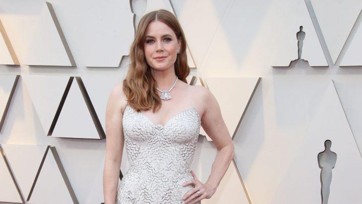 Peinados y looks que los Óscar 2019, Amy Adams con cabello pelirrojo ondulado abajo de los hombros y vestido blanco