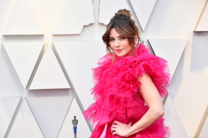 Peinados y looks que los Óscar 2019, Linda Cardellini con caberro recogido en chongo alto y despeinado, vestido rosa amplio de tul esponjado