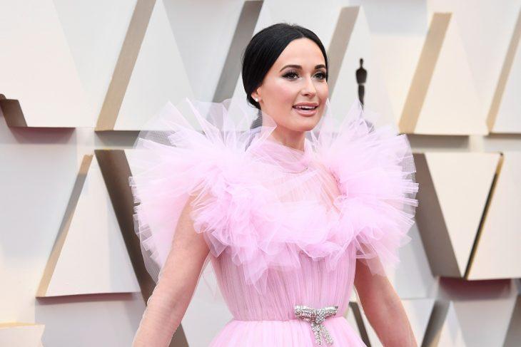 Peinados y looks que los Óscar 2019, Kacey Musgraves, cabello recogido en una coleta con vestido rosa de tul