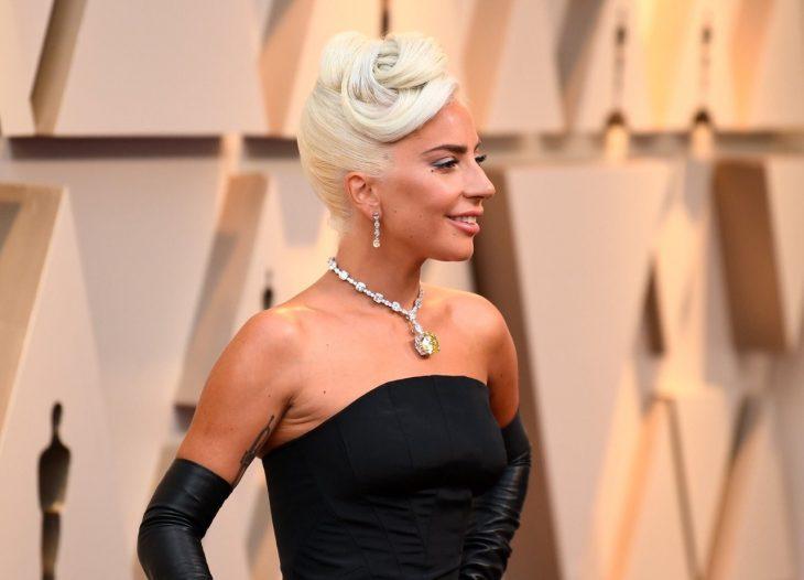 Peinados y looks que los Óscar 2019, Lady Gaga con peinado recogido estilo vintage romántico, vestido y guantes negros