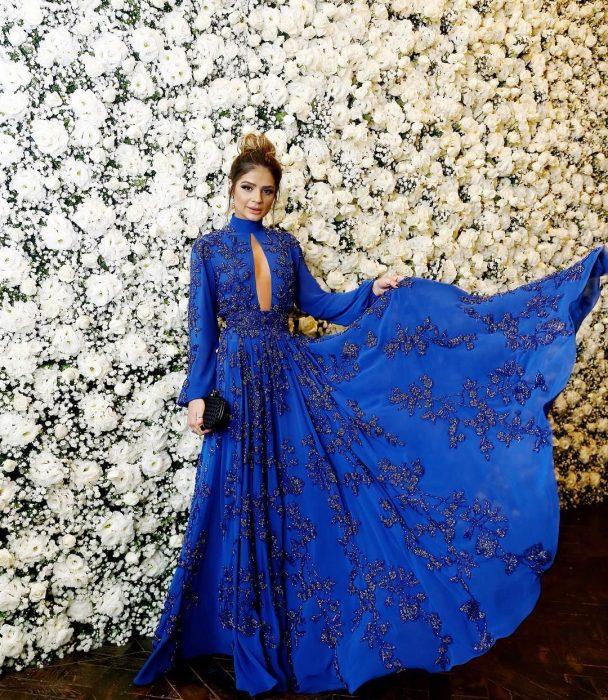 Chica con vestido de fiesta largo color azul royal con mangas y pedrería frente a una pared de flores blancas