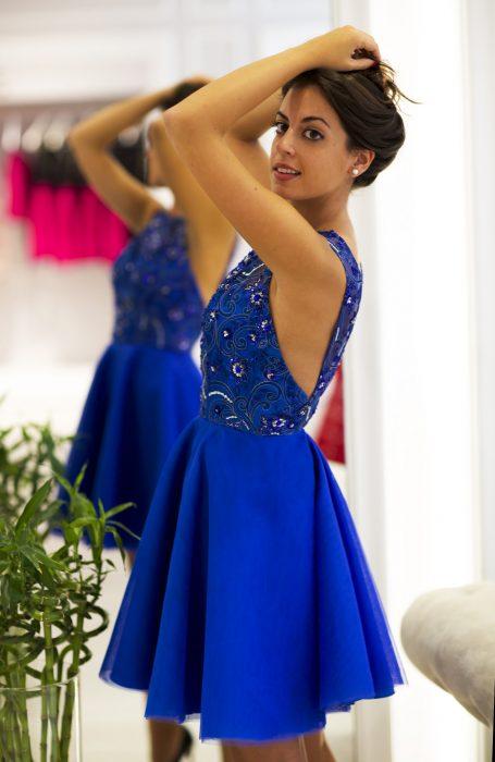 Chica de cabello castaño frente a un espejo con vestido de fiesta corto color azul royal con ornamentos y pedrería en la parte superior y sin mangas
