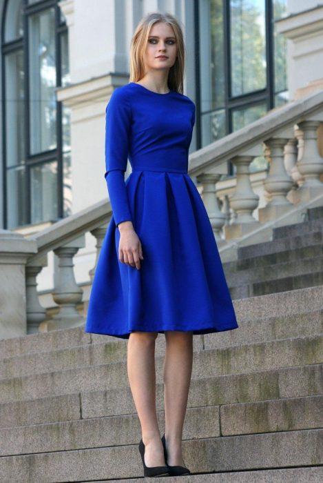 Mujer rubia en escaleras con vestido de fiesta o casual corto color azul royal con mangas y tacones negros