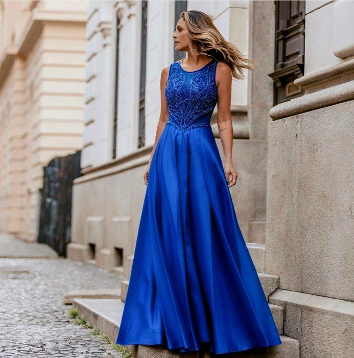 Mujer rubia parada en escalones con vestido de fiesta largo color azul royal sin mangas con ornamentos