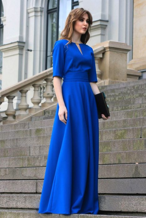 Chica de cabello castaño con fleco parada en escaleras usa vestido largo y sencillo color azul royal con mangas y cartera de mano