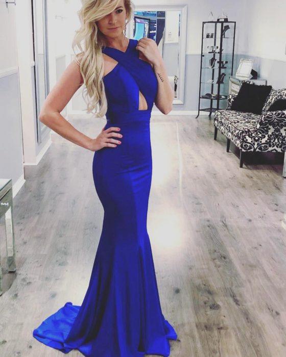 Chica rubia con vestido de fiesta largo color azul royal corte sirena con tirantes cruzados