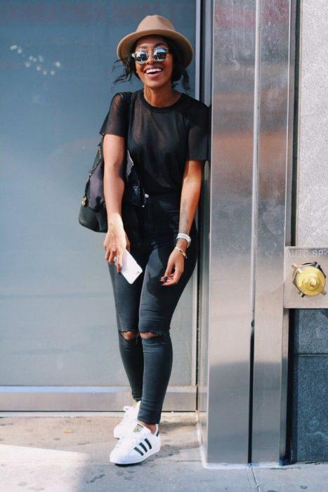 Chica recargada en pared usando pantalón negro rasgado, blusa negra, tenis blancos y sombrero café cálido