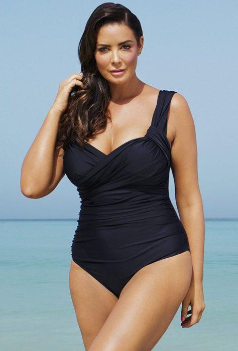 Chica en una playa posando con un traje de baño de color negro con drapeados