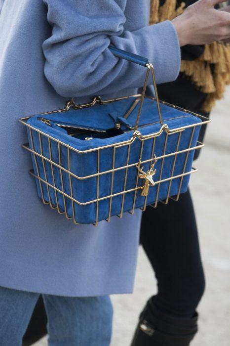 Chica sujetando unabolsa en forma de canasta de supermercado de color azul