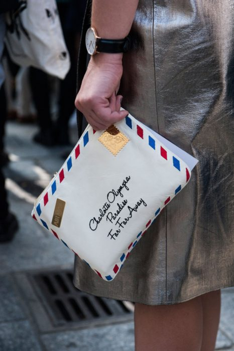 Chica sujetando una bolsa de mano en forma de carta