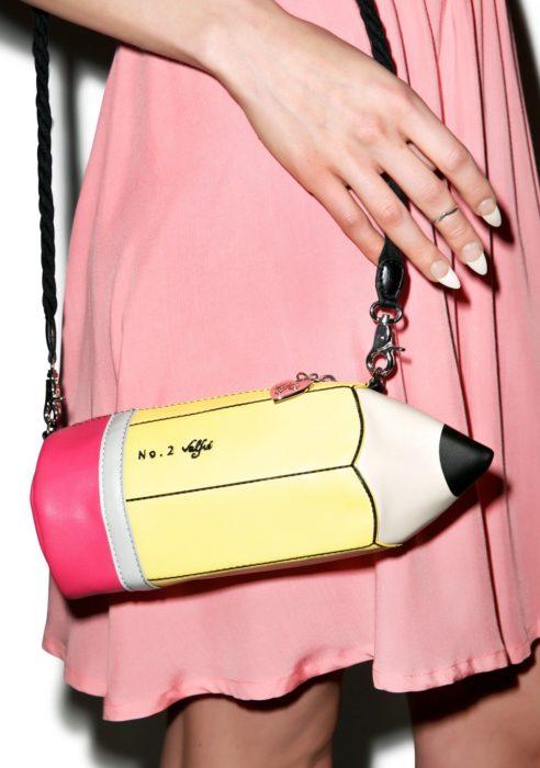 Chica sujetando un bolso de mano en forma de lápiz de escribir