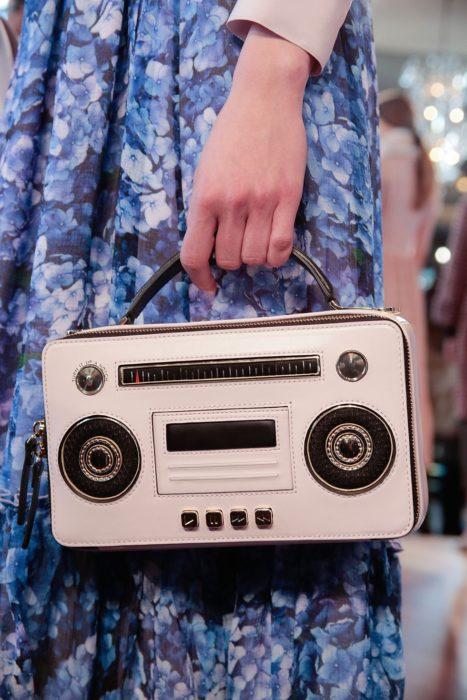 Chica sujetando un bolso con forma de grabadora de música