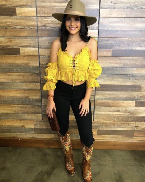 Chica usando una blusa amarilla, pantalón negro, sombrero y botas vaqueras