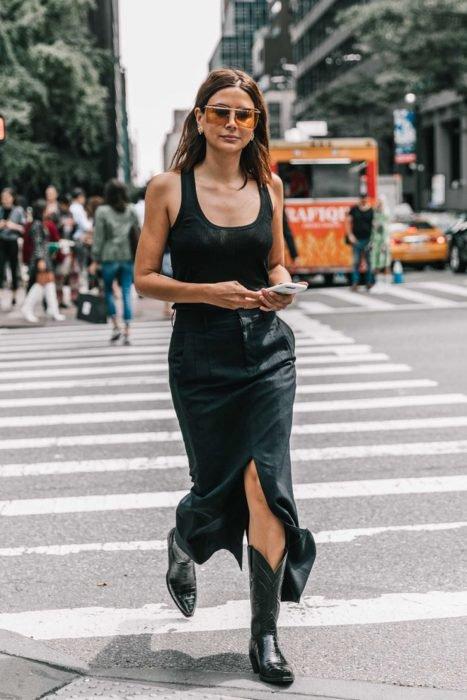 Chica usando un vestido negro con botas vaqueras
