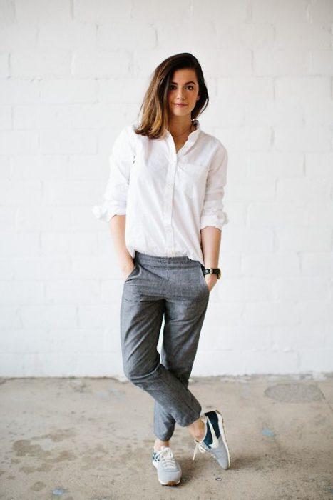 Chica usando pantalones de vestir color gris, blusa blanca y tenis de color verde