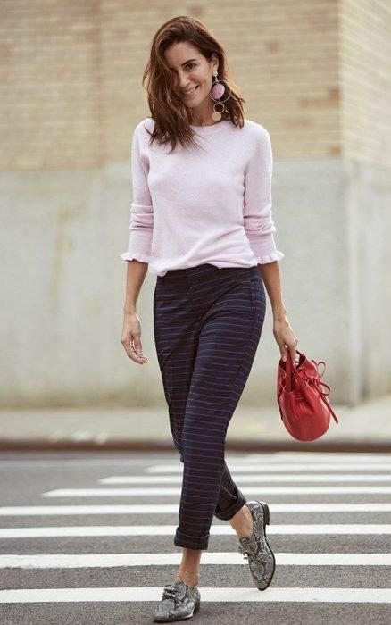 Chica caminando por la calle mientras usa una blusa rosa, pantalon de color morado con estampado de cuadros y zapatos animal print de color gris