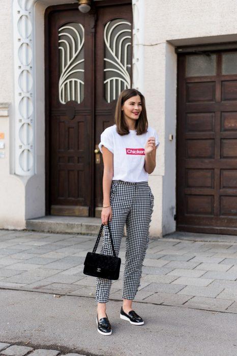 Chica usando unos pantalones de vestir con estampado cuadrado, camisa blanca y bolsa de mano de color negro