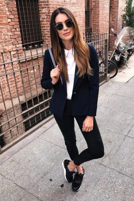Chica usando un traje de color negro con zapatos bajos de color negro