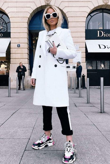 Chica usando un pantalón negro, saco blanco y ugly snekers
