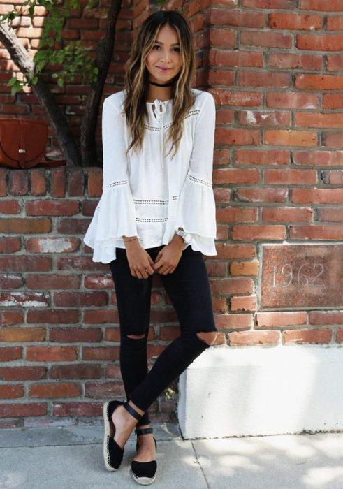Chica usando una blusa blanca, jeans negros y alpargatas en color negro