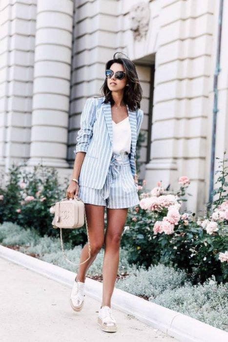 Chica usando un conjunto de color azul, bolso y sandalias