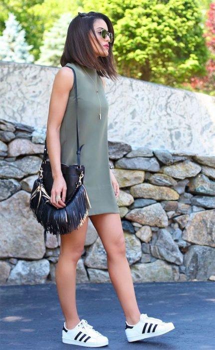 Chica usando un vestido de color verde, bolso negro y tenis adidas