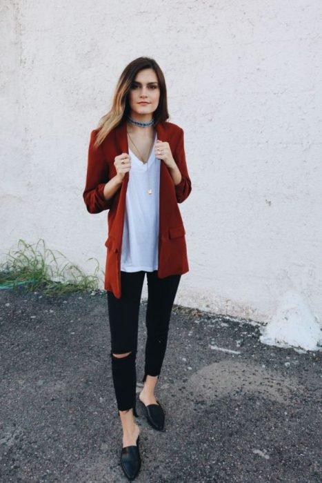 Chica usando un blazer de color rojo, jeans negros y mocasines