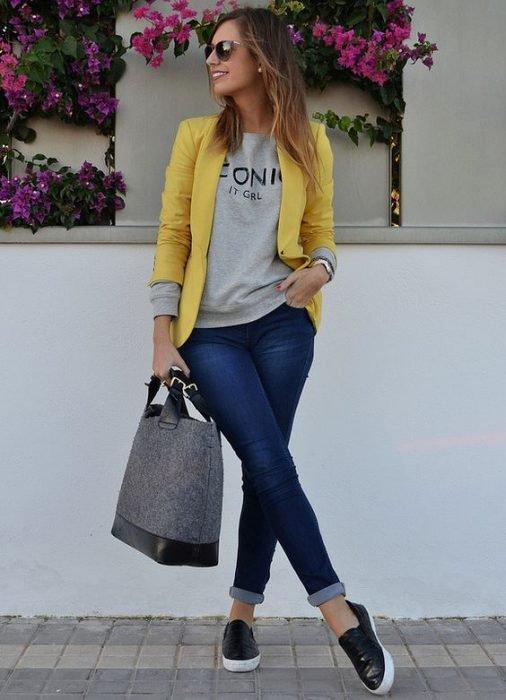 Chica usando un blazer amarillo, blusa de color amarillo y jeans