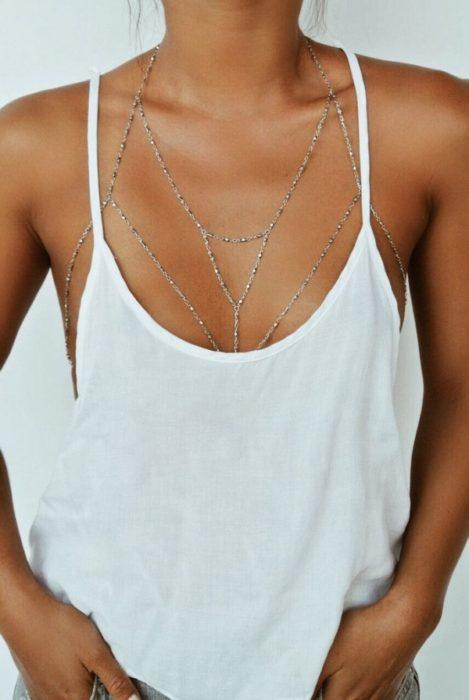 Torso de una mujer que usa un arnés a manera de cadena en el cuello y pecho