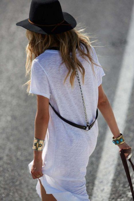 de espaldas una mujer con vestido de camiseta usa un arnés suelto en la cintura y sujeto por una cadena al cuello