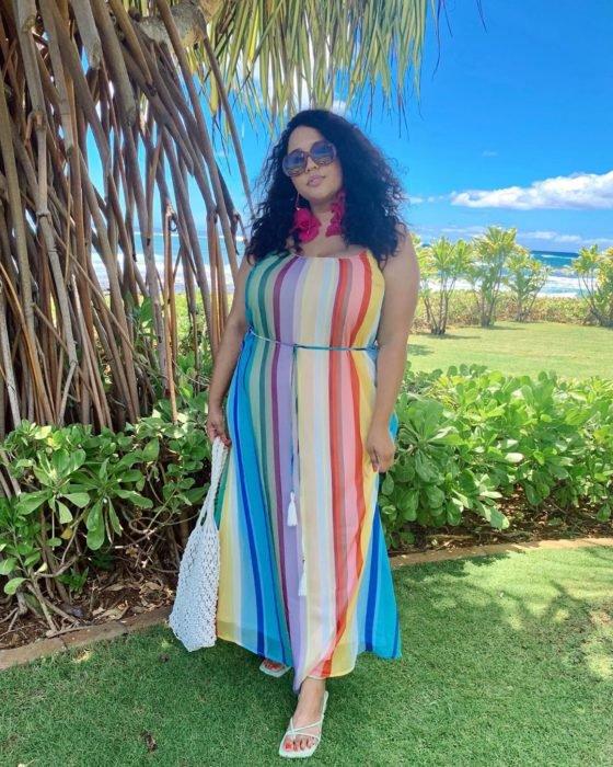 Una mujer en un campo con un vestido rayado de colores